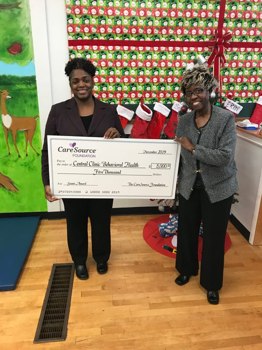 Vanessa R. Brown, LPCC, LICDC, CTP-C, Clinical and Program Director of the Family Healing Center, Central Clinic Behavioral Health (left) receives a check from Lera Battle (right), the CareSource Foundation.