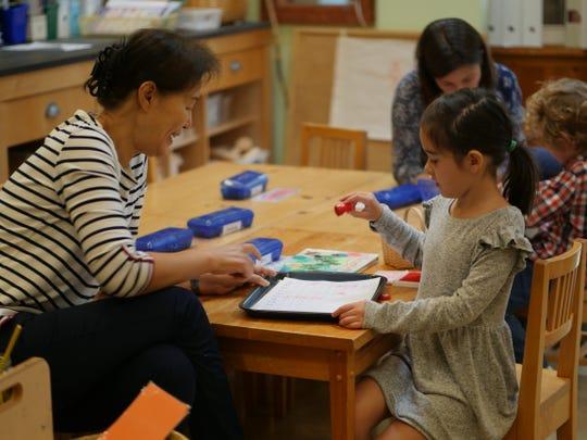 (Left to right)Willow kindergarten teacher Julie Kim of Bridgewater and Sydney Torrico of Califon work on a math game together.