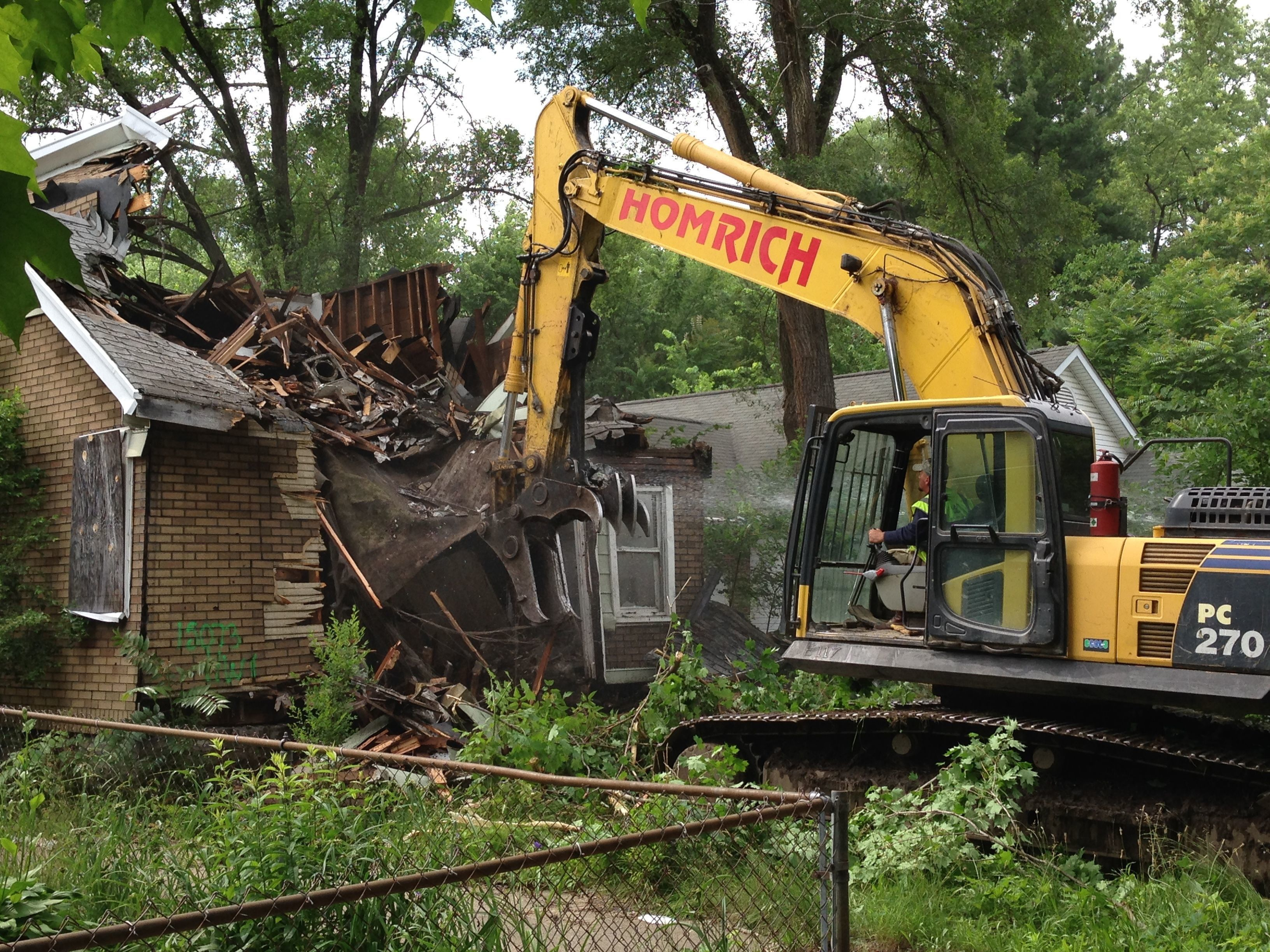 In this June 2015 photo, a contracted demolition crew from Detroit-based Homrich demolishes a house on Dolphin Street, as part of the city's blighted house demolition program.