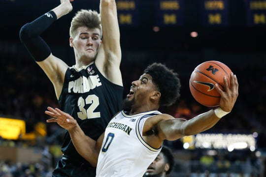 Michigan guard David DeJulius makes a layup against Purdue center Matt Haarms during the first half at Crisler Center in Ann Arbor, Thursday, Jan. 9, 2020.