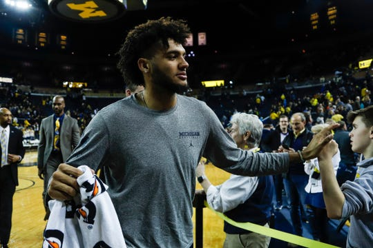 Michigan forward Isaiah Livers high fives fans as he walks back towards locker room after the Wolverines won 84-78 over Purdue at Crisler Center in Ann Arbor, Thursday, Jan. 9, 2020.
