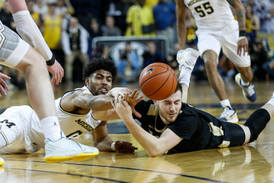 Michigan guard David DeJulius (0) and Purdue guard Sasha Stefanovic (55) battle for the loose ball during the second half at Crisler Center in Ann Arbor, Thursday, Jan. 9, 2020.