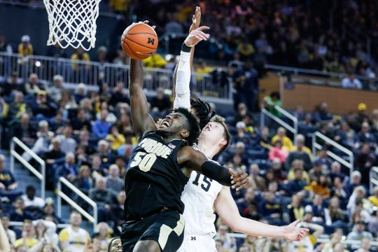 Purdue forward Trevion Williams (50) reaches for a defensive rebound in front of Michigan center Jon Teske (15) during the second half at Crisler Center in Ann Arbor, Thursday, Jan. 9, 2020.