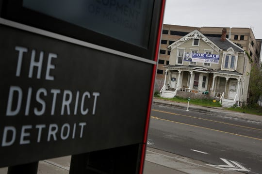 A new District Detroit is seen across from residential home for sale near Little Caesars Arena at 2712 Cass Avenue in Detroit on Monday, May 14, 2018.