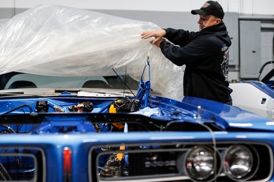 Dave Dudek takes the cover off a 1971 Dodge Charger R/T at Dave Dudek Muscle Cars garage in January in Clinton Township.