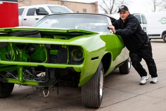 Dave Dudek pushes a newly arrived one of a kind 1970 Plymouth Barracuda with sassy grass green into his garage in Clinton Township, Tuesday, Jan. 7, 2020.