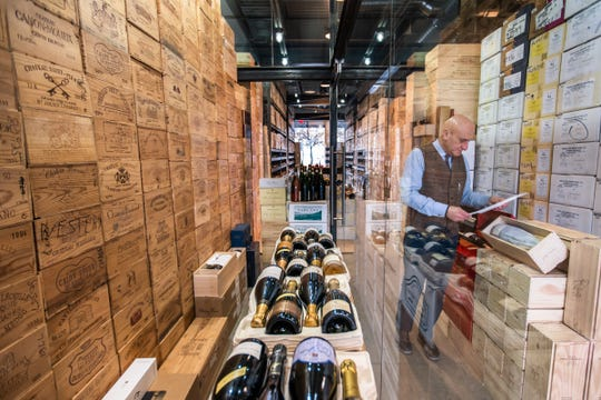 Elie Wine Company owner Elie Boudt arranges some bottles in his Birmingham shop on Friday. The wine industry is holding its breath on a proposed 100% tariff on European wines and other goods that could be imposed soon.