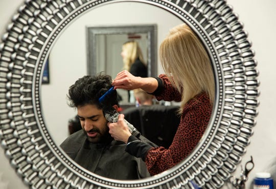 Kevin Mehra, 32, of Clawson gets his hair cut by stylist Alana Mechem, 52, of Canton at The Arena Barber House in Clawson Thursday, Jan. 9, 2020. This shop is one of many barbershops and hair salons popping up in southeast Oakland County.
