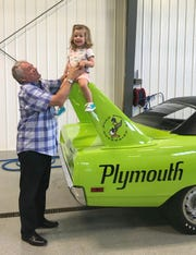 Peter Swainson with his granddaughter, Lara, in the summer of 2018 at his home in Red Deer, Alberta. They are standing with his 1970 Plymouth Superbird. Swainson is a top client of muscle car restoration specialist David Dudek, who lives in St. Clair Shores, Michigan.
