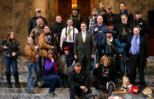 "In this Jan. 15, 2015, file photo, Washington state Rep. Matt Shea, R-Spokane Valley, in suit and yellow tie at center, poses for a group photo with gun owners inside the Capitol in Olympia, Wash., following a gun-rights rally. An investigative report prepared for the state Legislature and released Thursday, Dec. 19, 2019 said that Shea took part in ""domestic terrorism"" against the United States during a 2016 standoff at a wildlife refuge in Oregon and traveled throughout the West meeting with far-right extremist groups."