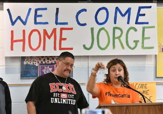 Cindy Garcia holds up the permanent resident card of her husband, Jorge Garcia, left, at a press conference.