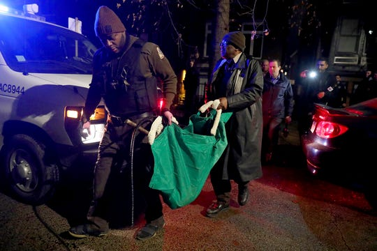 A Chicago police officer and a Chicago Animal Care and Control worker carry a coyote out in a green bag after tranquilizing the animal behind a home on Thursday, Jan. 9, 2020.