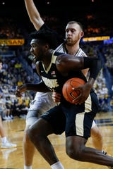 Purdue forward Trevion Williams makes a move on drives on Michigan forward Austin Davis Thursday night.
