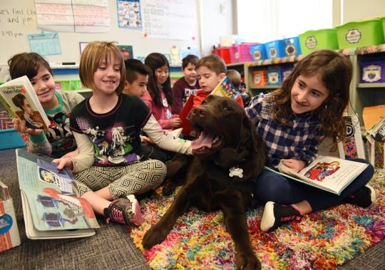 Sydney Latimer, left, 8, and Aina Malile, 7, read a story to Champ during class as Walled Lake's Mary Guest Elementary School students interact with the therapy dog, Wednesday, January 8, 2020.