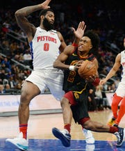 Cavs' Collin Sexton scores over Pistons' Andre Drummond in the second quarter.