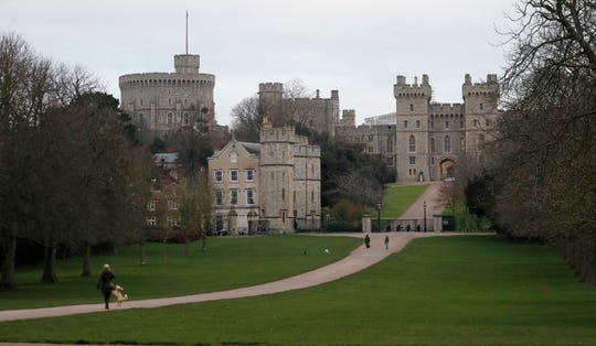 Pedestrians walk the Long Walk in front of Windsor Castle, near the Frogmore Cottage home of Britain's Prince Harry and Meghan Duchess of Sussex in Windsor on Friday.