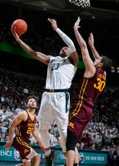 Michigan State's Xavier Tillman, left, shoots next to Minnesota's Alihan Demir during the second half Thursday. Tillman finished with 19 points and 16 rebounds in MSU's 74-58 victory.