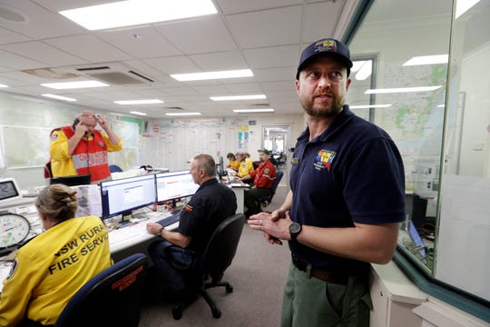In this Thursday, Jan. 9, 2020, photo, Terrance Gallegos, right, operations section chief at Santa Fe National Forest in the U.S., works in the situation room at the Rural Fire Service office in Moruya, Australia.