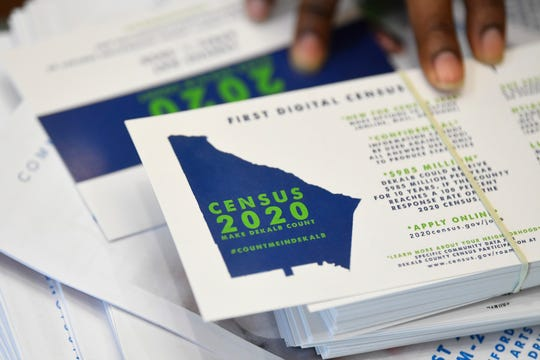 FILE - In this Aug. 13, 2019, file photo a worker gets ready to pass out instructions in how fill out the 2020 census during a town hall meeting in Lithonia, Ga.