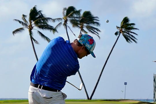 Zach Johnson hits from the 16th fairway on Thursday as heavy winds blow onto the palm trees.