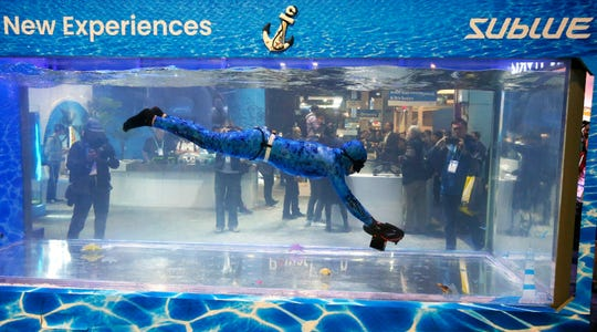 A Sublue diver moves around with the Sublue WhiteShark Mix outfitted with dual propellers for power and balance shown at their water tank booth during the CES tech show Wednesday, Jan. 8, 2020, in Las Vegas.