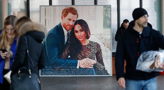 People walk past a picture of Britain's Prince Harry and Meghan Duchess of Sussex, in Windsor on Friday.