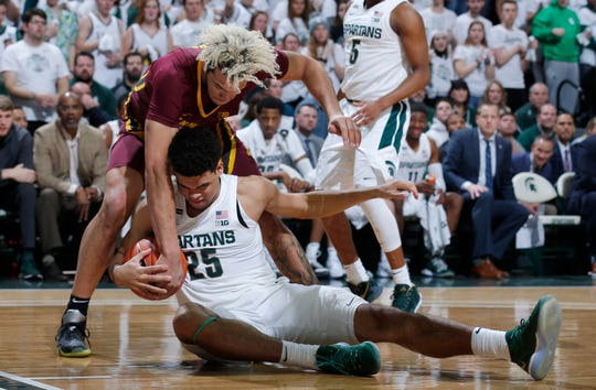 Michigan State's Malik Hall and Minnesota's Jarvis Omersa wrestle for the ball during the first half Thursday.