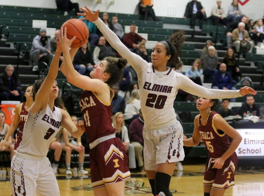 Georgia Haverlock of Ithaca takes a shot as Elmira's Zhane Holmes (3) and Zaria DeMember-Shazer (20) defend during the Express' 69-37 win in girls basketball Jan. 9, 2020 at Elmira High School.