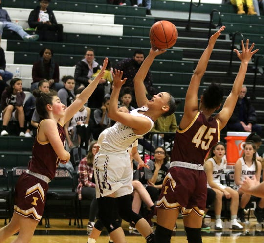 Elmira's Kiara Fisher squeezes off a shot in between Ithaca defenders Georgia Haverlock (left) and Ava Thomas (45) during the Express' 69-37 win in girls basketball Jan. 9, 2020 at Elmira High School.