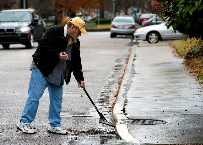 Jim Gerhardt rakes leaves from the street gutter near his home at the intersection of Mulberry and Frederick Streets Friday afternoon, Jan. 10, 2020. Gerhardt was preparing for more heavy rainfall Friday evening and throughout the day Saturday.