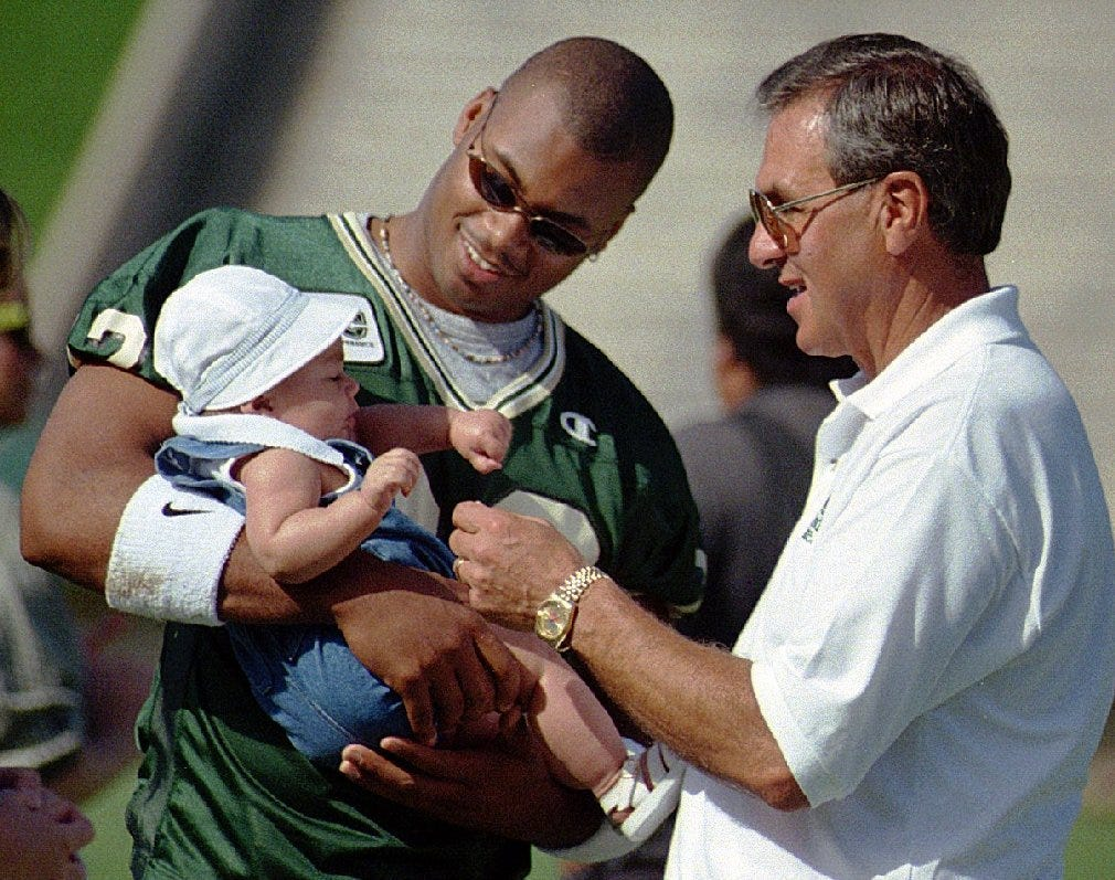 Sonny Lubick greets Jordan Ballard, Darrell Ballard's 4-month-old daughter. Players referred to Lubick as a 'father figure.'