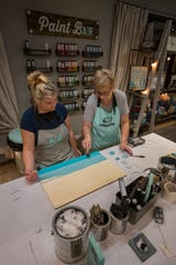 Cape Coral resident Amy Reppert, left, and team lead Francine Ross work on a wooden sign during a hands on class at AR Workshop in Cape Coral Thursday evening, January 09, 2020. The business offers its clients the opportunity to participate in hands-on DIY classes guiding them in the creation of a variety of custom home decor options from raw materials.