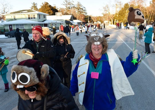 Groundhogs abound as Jerri Lee O'Malley of Baileys Harbor waves her groundhog pole while marching in a past Groundhog Day parade in Ellison Bay.