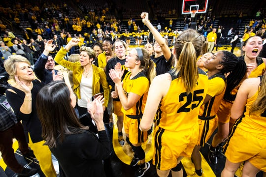 Iowa head coach Lisa Bluder, far left, and associate head coach Jan Jensen celebrate with players after Thursday's 66-61 upset of Maryland at Carver-Hawkeye Arena.