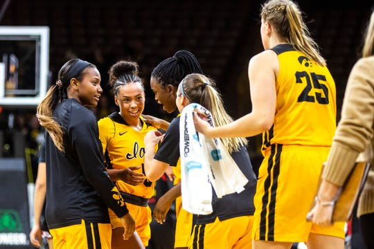 Iowa guard Alexis Sevillian (5) is embraced by teammates heading into a timeout during a NCAA college Big Ten Conference women's basketball game, Thursday, Jan. 9, 2020, at Carver-Hawkeye Arena in Iowa City, Iowa.
