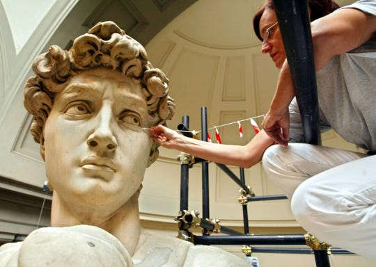 "Italian restorer Cinzia Parnigoni cleans the ""David"" in 2003 at the Galleria del'Academia in Florence."