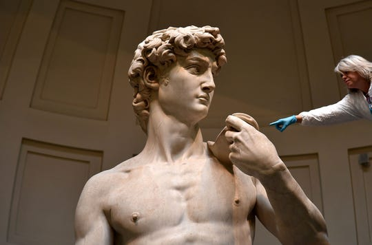 "An Italian restorer cleans Michelangelo's ""David,"" one of the world's most famous statues, at the Galleria dell'Accademia in Florence in 2016."