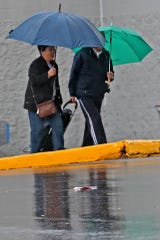 People stay under cover as they walk in the rain a strip mall parking lot near 86th and Michigan, Friday, Jan., 10, 2020.