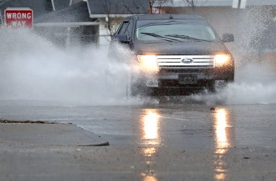 A car splashes on 30th St., as rain continues to fall, Friday, Jan., 10, 2020.
