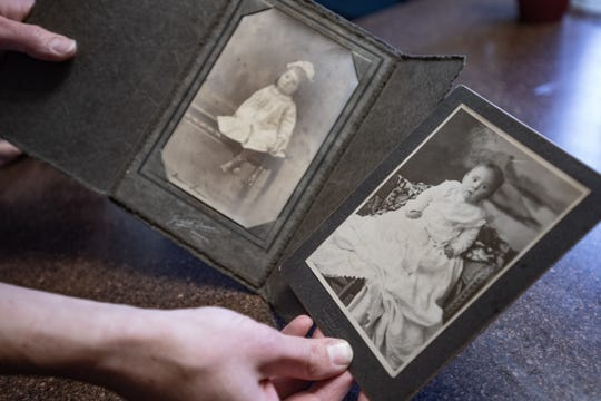 Rachel Morris of Eaton Rapids shows vintage photos Friday, Jan. 10, 2020, that she and her husband found along with a letter in a home they are renovating in northwest Lansing.