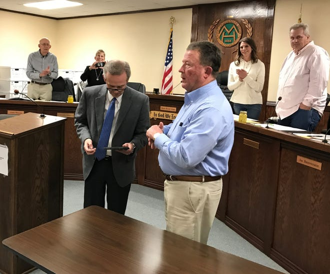Mountain Home City Attorney Roger Morgan (left foreground) was recognized for 30 years of service to the city Thursday night with a plaque and a gift by Mayor Hillrey Adams (right foreground). Standing behind them are City Council members (from left) James Whalen, Jennifer Baker, Paige Dillard Evans and Don Webb.