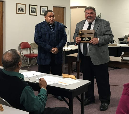 Morehouse Parish Superintendent David Gray, right, presents Louis Melton a plaque for his service as president of the Morehouse Parish School Board.