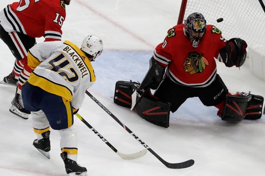 Chicago Blackhawks goalie Corey Crawford, right, cannot make the stop on a goal by Nashville Predators center Colin Blackwell (42) during the first period in Chicago, Thursday, Jan. 9, 2020.
