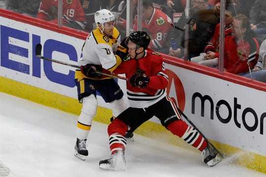 Nashville Predators center Kyle Turris, left, and Chicago Blackhawks defenseman Connor Murphy battle for the puck during the first period in Chicago, Thursday, Jan. 9, 2020.