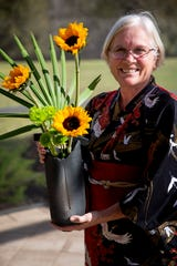 Margy Metzler poses for a photo with one of her arrangements at her home in Fort Myers on Thursday, January 9, 2020.