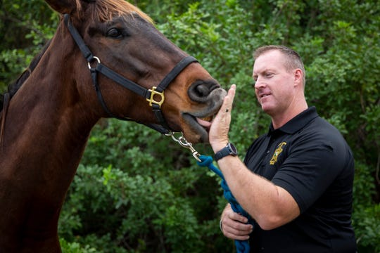 "Maverick licks Lee County Sheriff's Office Cpl. Aaron Eubanks' hand at his home in Naples on Friday, Jan. 10, 2020. ""He won't take treats, but he'll always lick my hand,"" Eubanks said."