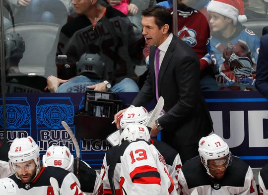 New Jersey Devils interim head coach Alain Nasreddine, top, directs his players during a time out against the Colorado Avalanche in the first period of an NHL hockey game Friday, Dec. 13, 2019, in Denver.