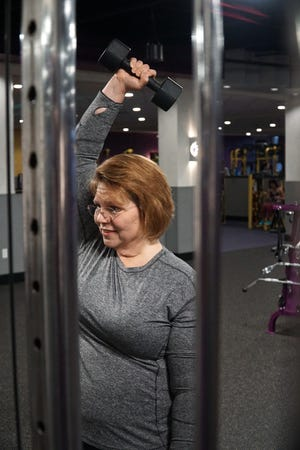 Christine Hoke uses some free weights at a Wixom Planet Fitness.