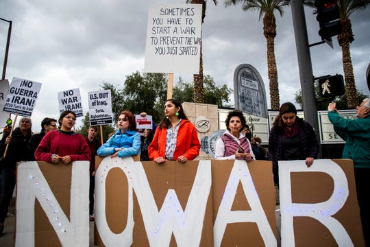 People protest the Trump administration's killing of a top Iranian general and decision to send 3,000 more soldiers to the Middle East on the corner of Camelback and 24th Street in Phoenix on Thursday, Jan. 9, 2020.