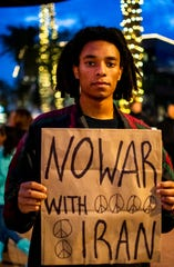 In a Jan. 9 photo, Jayvan Bailey poses for a portrait with an anti-war sign in Phoenix, protesting the Trump administration's killing of a top Iranian general and decision to send 3,000 more soldiers to the Middle East.